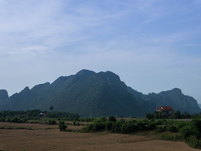 Flat rice paddies with huge limestone towers full of undiscovered caves.